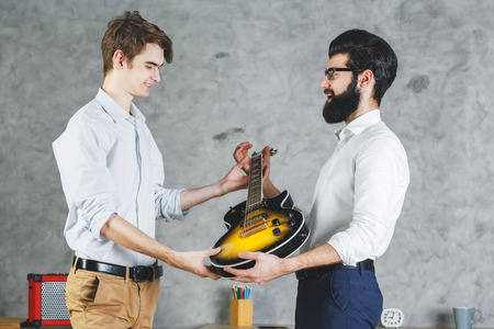 rehearse: Attractive businessmen playing with guitar in office interior with desk and concrete wall background. Leisure, music, rehearsal, band concept