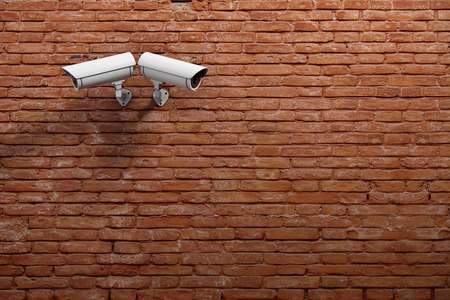 Two white CCTV cameras on red brick wall background with copyspace. Technology concept. 3D Rendering Stock Photo