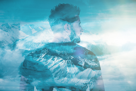 Back view of young european man on creative snowy winter mountain landscape background. Freedom concept. Double exposure Stock Photo