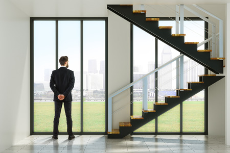 Back view of young businessman in modern interior with stairs and city view. Research concept. 3D Rendering