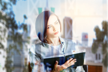 info: Portrait of pretty young woman reading book on abstract summer city background. Education concept. Double exposure
