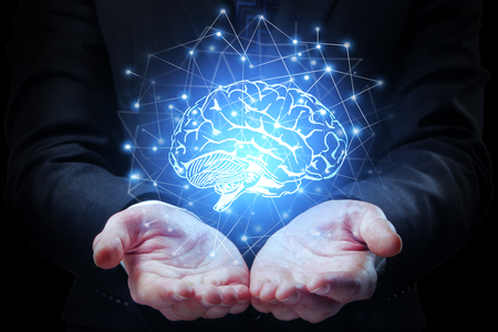 Businessman hands holding abstract polygonal brain on dark background. Artificial mind concept