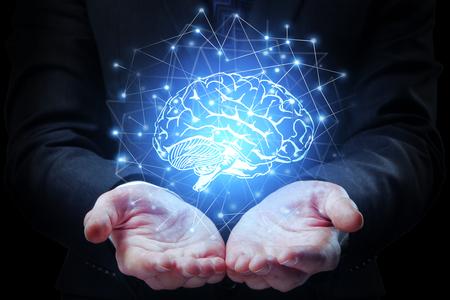 Mãos de empresário segurando cérebro poligonal abstrato sobre fundo escuro. Conceito de mente artificial