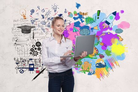 drawing room: Smiling young businesswoman with laptop standing on concrete wall background with business sketch. Education concept