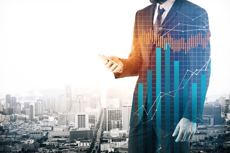 Businessman using smartphone with abstract forex chart on city background. Trade concept. Double exposure Stock Photo
