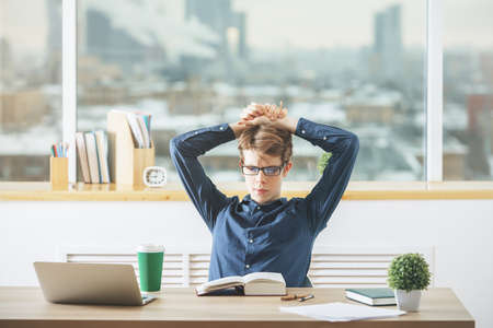 marketing online: Portrait of young man working on project at modern desk with laptop, paperwork, supplies, coffee cup and other items