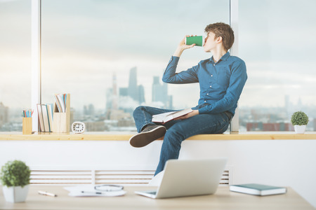 cup: Handsome young businessman reading book and drinking coffee in modern office with blurry city view. Leisure concept