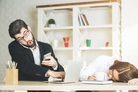 Surprised businessman and woman using smartphone at modern office workplace. Leisure, break, distraction, social media, technology and communication concept Stock Photo