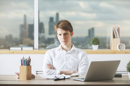 marketing online: Portrait of young european male working on project at modern office desk with laptop, paperwork, supplies and other objects