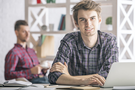 Portrait of handsome european boy using laptop at workplace. Technology and communication concept Stock Photo