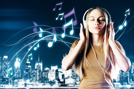 Relaxed european woman listening to music on night city background. Hobby concept