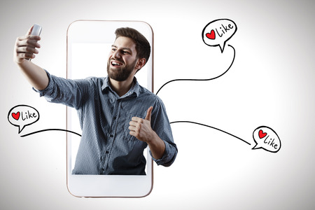 Cheerful young man with smartphone getting likes. Social media and communication concept