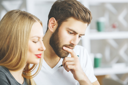 Side portrait of smiling thoughtful european man and woman in blurry office. Teamwork and partnership concept Stock Photo
