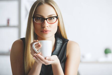 Close up portrait of confident caucasian female drinking coffee on blurry office background. Morning, drink, break, lifestyle concept