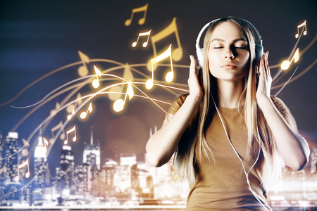 eyes are closed: Relaxed white woman listening to music on night city background. Hobby concept