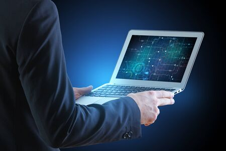 technology background: Businessman holding laptop with circuit on screen. Blue background. Technology and computing concept Stock Photo