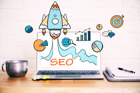 Close up of creative designer desktop with SEO spaceship hologram on laptop screen, coffe cup and other items on white brick wall background. Startup and web concept