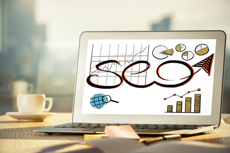 Close up of creative office desktop with SEO sketch on laptop screen, coffee cup and other items on blurry city background. Technology concept 版權商用圖片