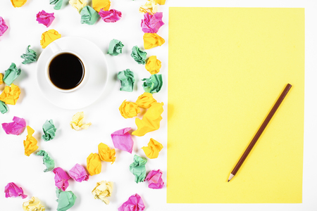 Top view and close up of messy white office workplace with various colorful supplies and coffee cup