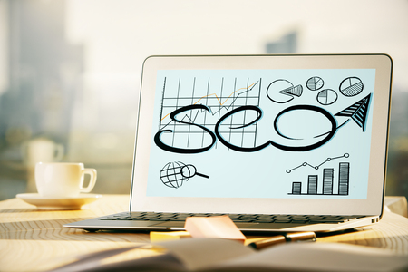 technology background: Close up of creative office desktop with SEO sketch on laptop screen, coffee cup and other items on blurry city background. Web concept