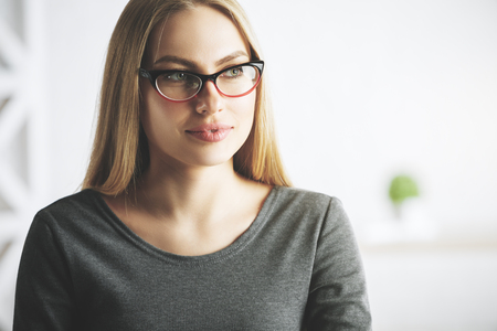 pondering: Close up portrait of attractive woman with glasses in modern office. Blurry background. Worker concept