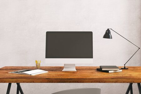 technology background: Close up of creative designer desktop with empty computer screen, supplies, table lamp and other items on concrete wall background. Mock up, 3D Rendering