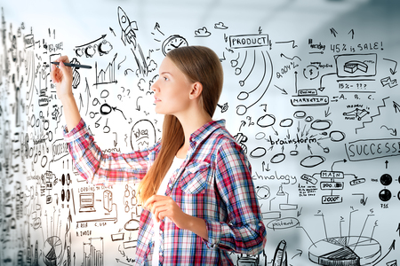 technology background: Side view of young european woman drawing business sketch on blurry interior background. Success concept