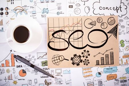 technology background: Top view of office workplace with coffee cup, pen and business SEO sketch. Internet concept