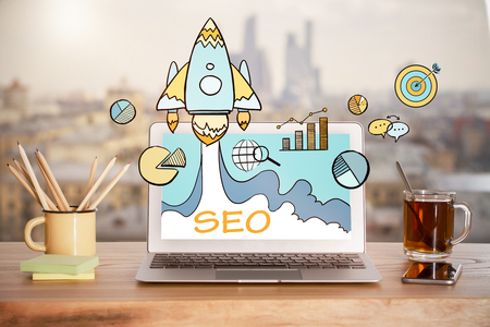 Close up of creative designer workplace with SEO rocket hologram on laptop screen, smartphone, tea cup and other items on blurry city background. Startup and marketing concept