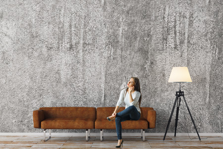 Thoughtful woman sitting in concrete living room interior with empty wall, couch and floor lamp. Comfort and relaxation concept. Mock up, 3D Rendering Stock Photo