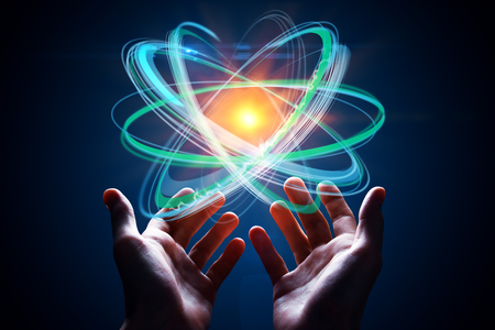 Hands holding abstract digital atom on blue background. Future concept. 3D Rendering Stock Photo