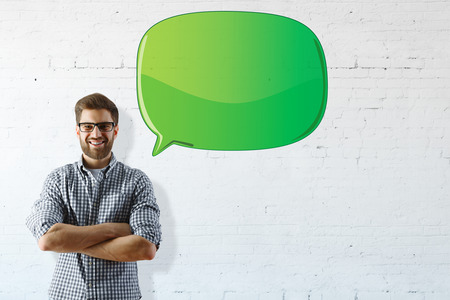 arms folded: Portrait of happy smiling man with folded arms standing on brick wall background with empty speech bubble. Mock up Stock Photo
