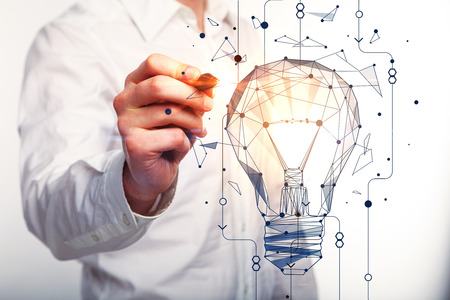 Businessman drawing abstract polygonal lamp on light background. Innovation concept