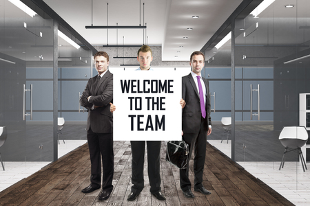 Three handsome european businessmen standing in office corridor interior with text on banner. Teamwork, 3D Rendering