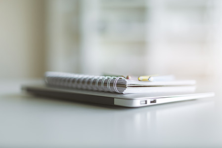 electronic book: Close up of stacked laptop, spiral notepad and other items on blurry office desktop Stock Photo