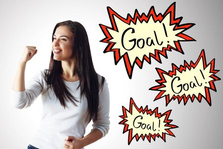 Excited young woman celebrating success on white wall background with exclamation comic speech goal bubble. Achievement concept Stock Photo