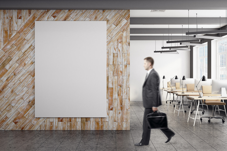 Side view of blurry young businessman walking in in modern coworking office interior with blank banner. Mock up, 3D Rendering