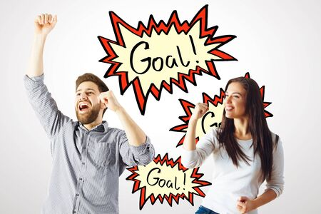dynamite: Excited young man and woman celebrating success on white wall background with exclamation comic speech goal bubble. Successful concept