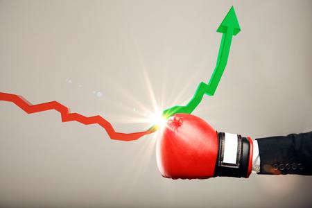 Rękawica bokserska przebijająca czerwoną strzałkę skierowaną w dół i zmieniająca się w zieloną wznoszącą się na jasnym tle. Kryzys gospodarczy i koncepcja sukcesu