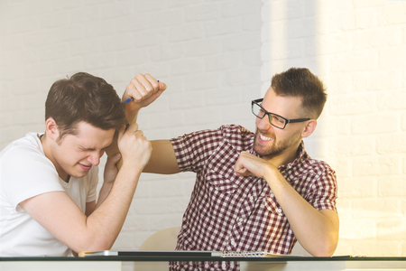 Two violent males beating each other in modern office. Rivalry and competition concept