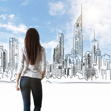 Back view of thoughtful young woman looking at drawn city on blue sky background Stock Photo