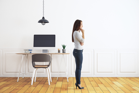 Side view of thoughtful young woman standing in modern white interior with workpace and wooden floor. Mock up, 3D Rendering