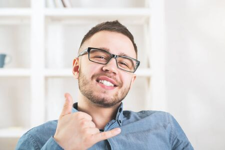 Portrait of attractive young businessman with call me gesture in blurry office. Success and hipster concept  Stock Photo