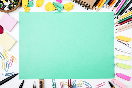 Top view of creative office workplace with colorful supplies and empty paper sheet with copy space. Mock up. Marketing and text concept  Stock Photo