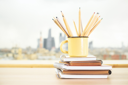 Close up of iron mug with pencils and spiral diary on blurry city view background. Supplies, stationery items and tools concept