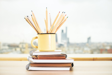 Close up of iron mug with pencils and spiral copybook on blurry city view background. Supplies, stationery items and tools concept