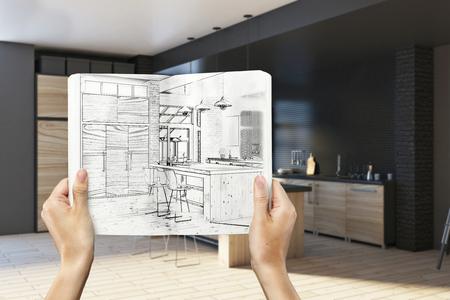 손에 흐린 내부 배경에 그리기 창조적 인 부엌 디자인 메모장을 들고. 건축 및 엔지니어링 개념입니다. 3D 렌더링