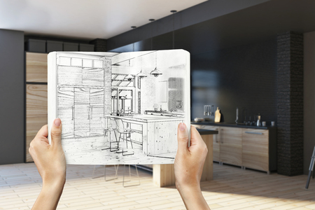 Hands holding notepad with creative kitchen design drawing on blurry interior background. Architecture and engineering concept. 3D Rendering