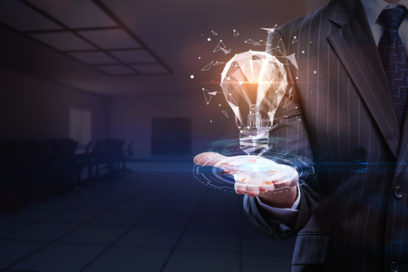 Businessman holding abstract glowing polygonal lamp on blurry office interior background. Innovation and success concept. 3D Rendering  写真素材