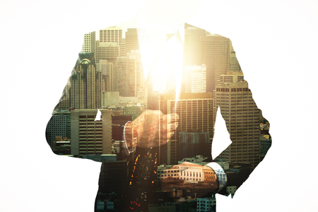 Unrecognizable businessman on abstract city background with sunlight. Success and career concept. Double exposure